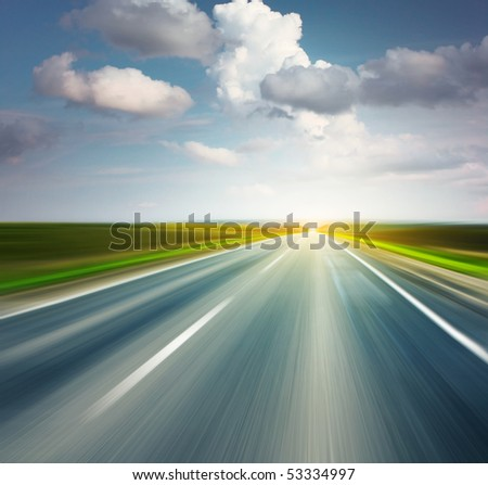 Empty asphalt road with cloudy sky and sunlight - stock photo