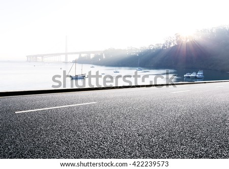empty asphalt road with sail boat on tranquil water and distant gold gate bridge  - stock photo