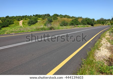 Empty asphalt two-way traffic road with a double solid white line and side restrictive yellow line. Hillbilly landscape surroundings. Road markings.Transportation and environment  theme - stock photo