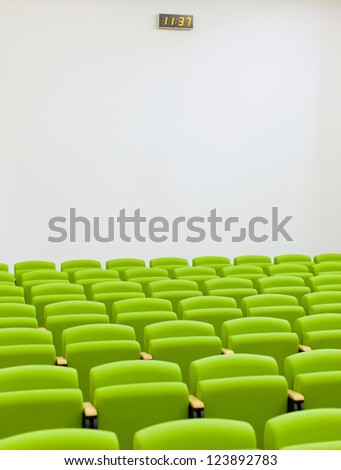 Empty auditorium with green chairs - stock photo