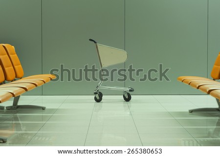 Empty baggage cart and the rows of chairs at the airport - stock photo