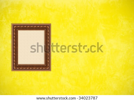 Empty baroque picture frame with copyspace on a yellow grunge stucco wall - stock photo