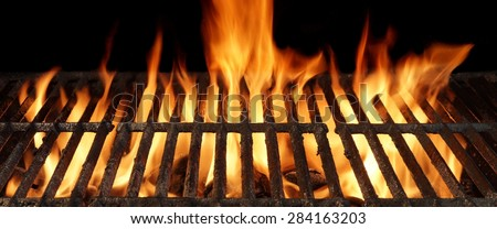Empty BBQ Charcoal Cast Iron Grill Close-up With Bright Flames On The Black Background. Outdoor BBQ Party Or Picnic Concept - stock photo