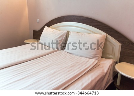 Empty bed in a hotel bedroom with soft cushions - stock photo