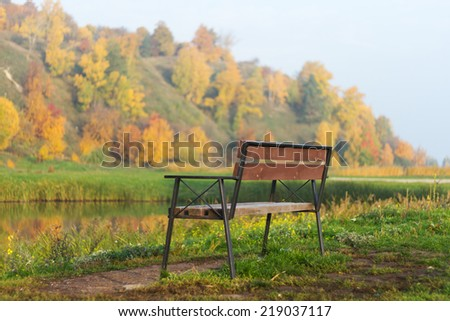 Empty Bench in the autumn park - stock photo