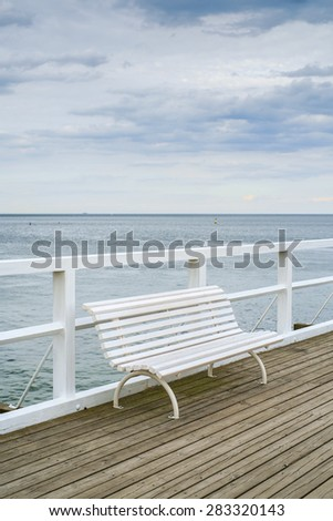 Empty bench on a pier. - stock photo