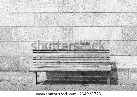 empty bench over stone wall - stock photo