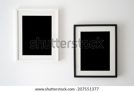 empty black and white picture frames on the wall - stock photo