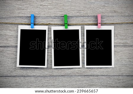 empty black photo frames hanging with clothespins on wooden background - stock photo