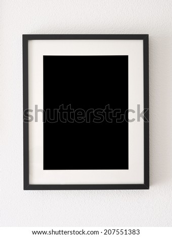 empty black picture frame on the wall - stock photo