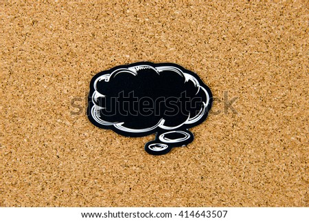 Empty black speech bubble over cork board background, copy space available - stock photo