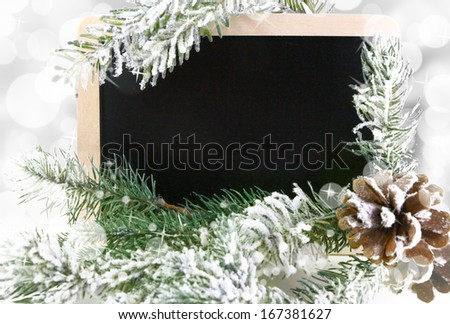 Empty blackboard with snowy Christmas tree and bokeh background - stock photo