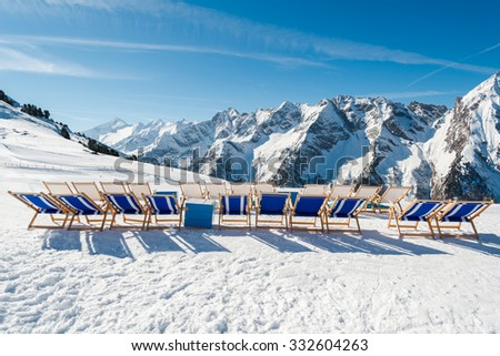 Empty blue deck chairs on the snow in Mayrhofen ski resort, Austrian Alp - stock photo