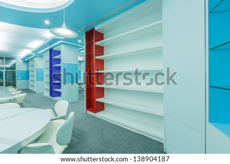 empty blue red and white book shelf in the empty modern library - stock photo