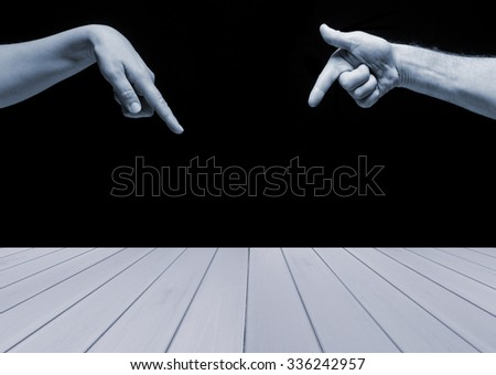 Empty blue wooden  table with man and woman hands pointing  on it on black background. Ready for product display montage. - stock photo