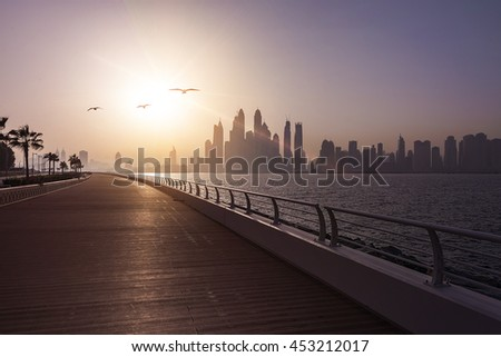 empty boardwalk in the morning sun with the skyline of Dubai in the background, Dubai, UAE - stock photo