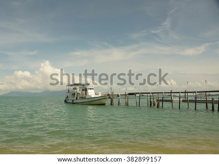 Empty boat standing at wooden pier under bright sunlight sea blue sky and water Thailand Asia Ko Samui - stock photo