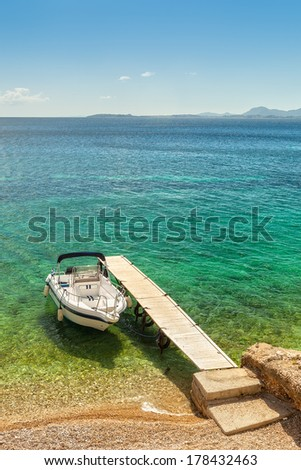 Empty boat standing at wooden pier under bright sunlight with shadow on pebbles at sea floor seen through transparent water of Ionian sea, Corfu, Greece - stock photo