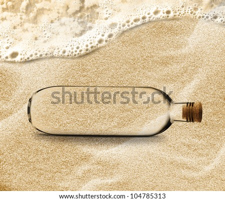empty Bottle in the beach sand with copy space to add your message inside the Bottle. - stock photo