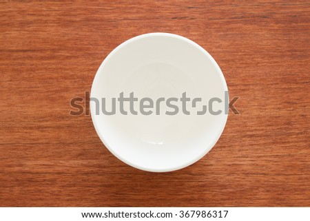 Empty bowl on a wooden board - stock photo