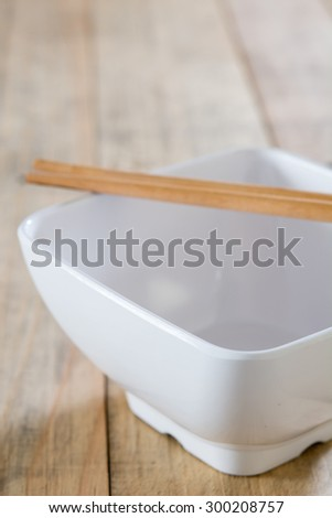 empty bowl with chop sticks on wooden - stock photo