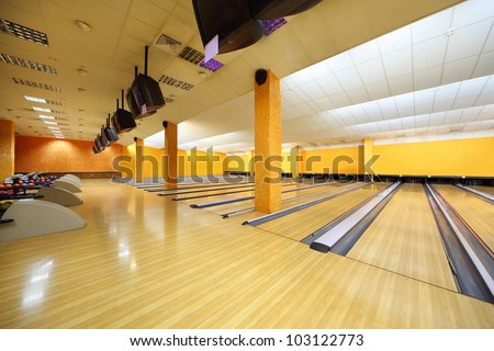 Empty bowling club, lot of bowling lanes with skittles, yellow walls and floor - stock photo