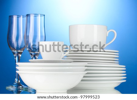 empty bowls, plates, cups and glasses on blue background - stock photo