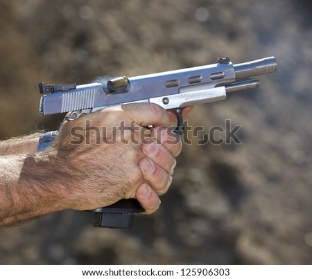 Empty brass shell being ejected from a semi automatic pistol - stock photo