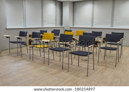 Empty bright lecture hall with chairs. Grey black yellow tones - stock photo