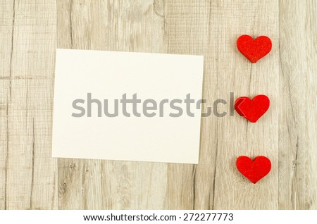 Empty card with heart on wooden background - stock photo