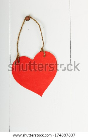 Empty cardboard heart hanging with string and nail, on wooden background, painted with white color - stock photo