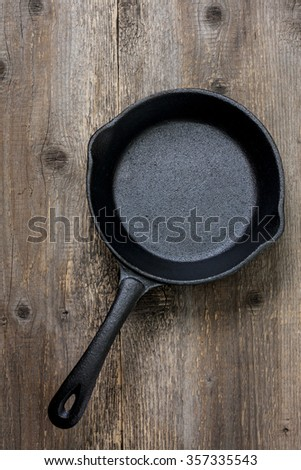 empty cast-iron pan on the old wooden background - stock photo