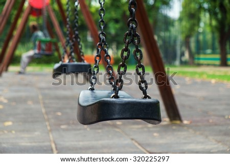 Empty chain swing in playground in city - stock photo