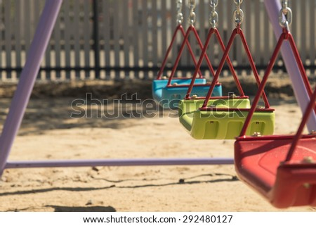 Empty chain swings on summer kids playground,vintage filter - stock photo