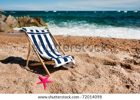 empty chair with towel at the tranquil beach - stock photo