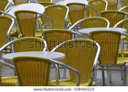 Empty chairs and tables in a bar terrace - stock photo