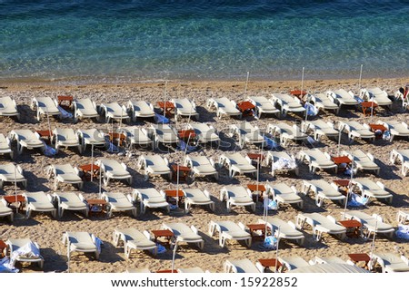 Empty chaise lounges on a morning beach - stock photo