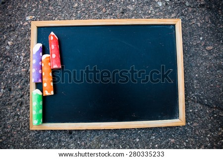 Empty chalkboard on asphalt with colorful street chalk - stock photo