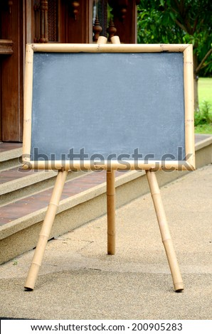 Empty Chalkboard with Bamboo Wood Stand Outdoor. - stock photo