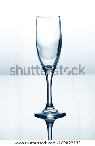 Empty champagne glass on blue and white gradient background - stock photo