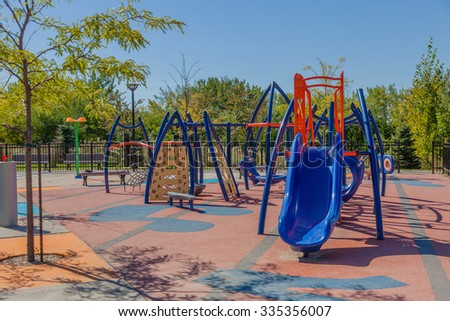 Empty children playground with ladders, climbing stairs, ropes and slides. Kids and toddlers place to have fun and play in summer. Bright sun, clear sky, hard shadows. - stock photo