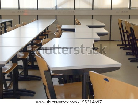empty classroom filled with desks and chairs  - stock photo