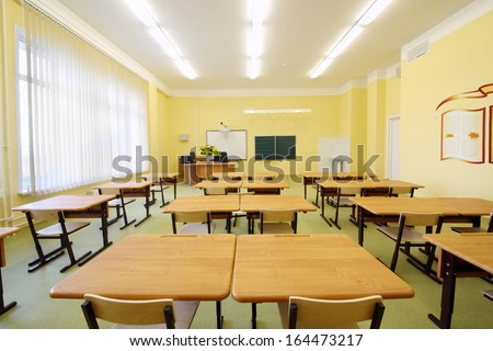 Empty classroom with wooden desks, white and green chalk boards in school. - stock photo