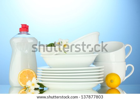 empty clean plates and cups with dishwashing liquid and lemon on blue background - stock photo