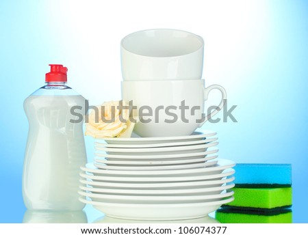 empty clean plates and cups with dishwashing liquid and sponges on blue background - stock photo