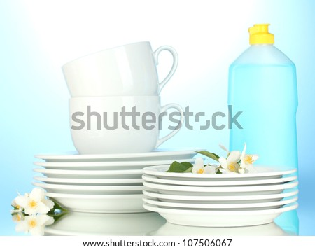 empty clean plates, cups and glasses with dishwashing liquid and sponges on blue background - stock photo