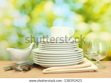 empty clean plates, glasses and cup on wooden table on green background - stock photo