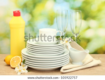 empty clean plates, glasses and cups with dishwashing liquid and lemon on wooden table on green background - stock photo