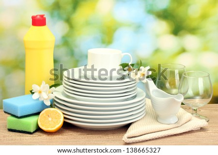 empty clean plates, glasses and cups with dishwashing liquid, sponges and lemon on wooden table on green background - stock photo