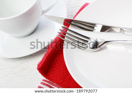 Empty coffee cup and plate on red napkins - stock photo
